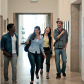 Students walking through a hallway laughing.