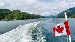 The wake of a ship on a big river, one half of a Canadian flag can be seen floating in the wind.