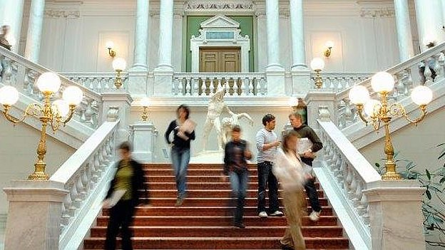 Students walking down a stairway in a venerable building