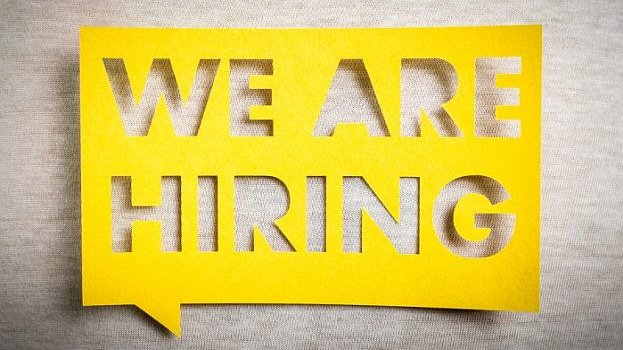 A yellow cardboard in front of a beige carpet, the words 'we are hiring' cut out of the cardboard.