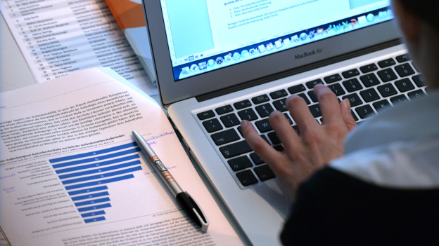 A person is typing into a laptop, a research paper lies next to the laptop.