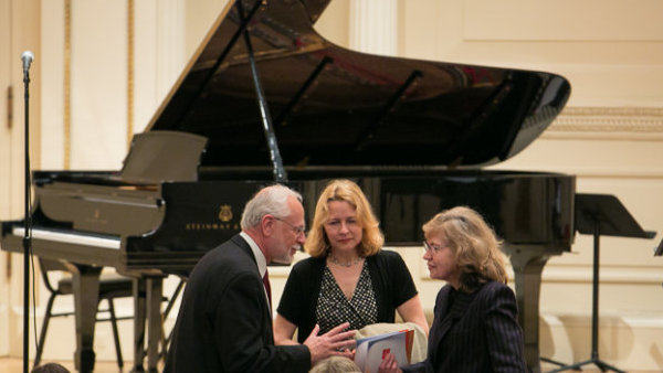 Three people in formal attire sitting and talking in front of a piano.