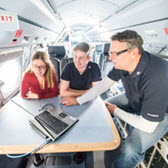 Professor showing two students something on a laptop, they are inside of an airplane.