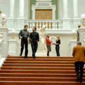 Two students walking down a wide staircase.