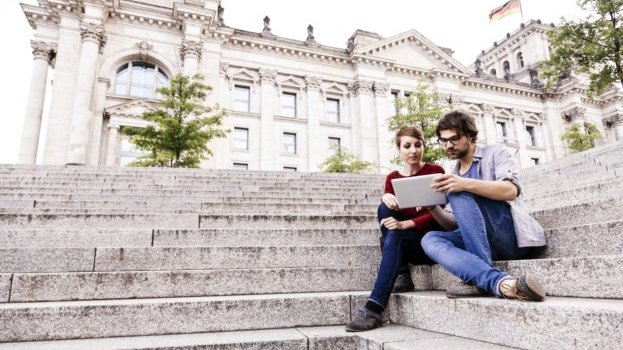 A boy and girl are sitting on stairway in front of the Bundestag and reading something together.