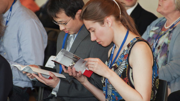 Two conference participants reading in flyers.