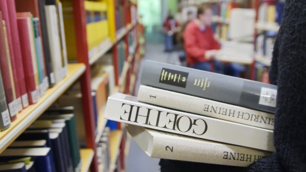 Close up of four books being held in an library