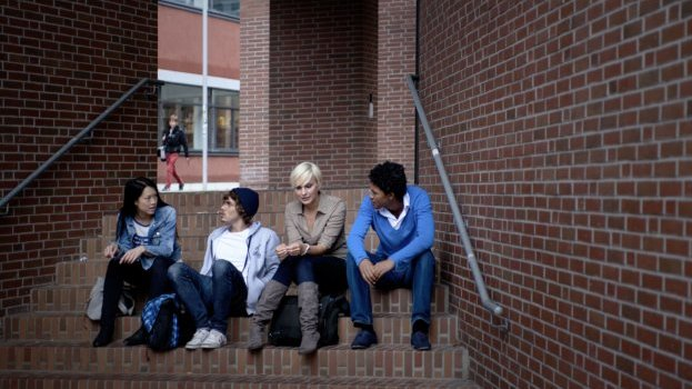 Students sitting on the stairs of a red brickwork building.