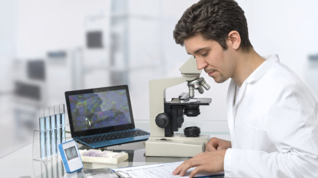 A young scientist with a lab coat, surrounded by lab equipment and a laptop.