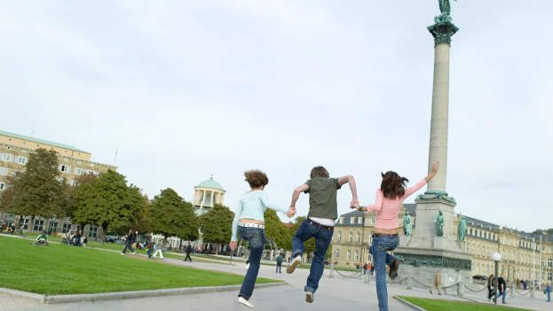 Students are joyfully jumping into the air in a park in Stuttgart.