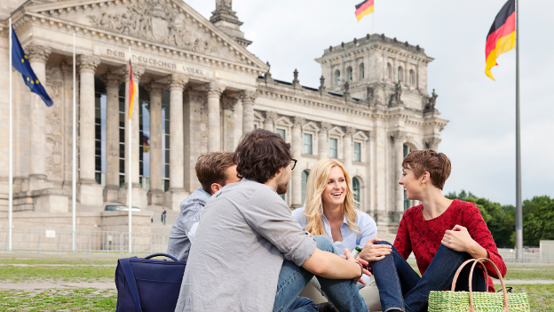 Four students are sitting in front of the Reichstag building in Berlin.