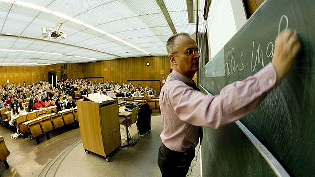 A professor is writing onto a blackboard in the front of a crowded lecture hall.