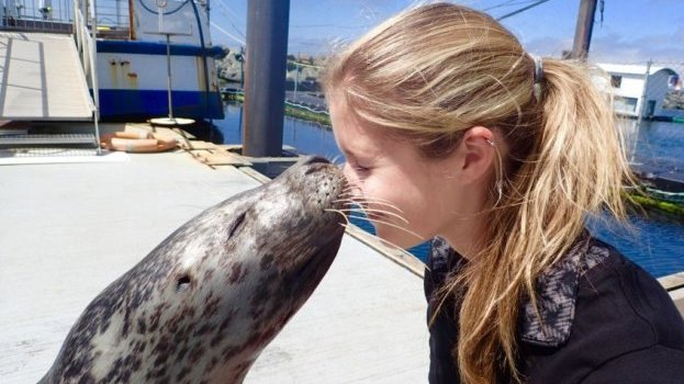 A girl playing with a seal on the deck of a boat.