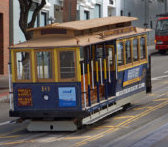 Cable car driving on an uphill street in San Francisco.