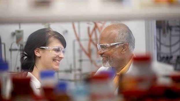 Two scientists in a lab smiling at each other.