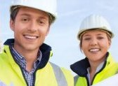 Two smiling persons with safety vest and safety helmet.