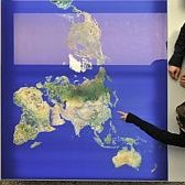 Two people in front of a map of the world, seen from above.