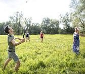 Students playing badminton in a park.