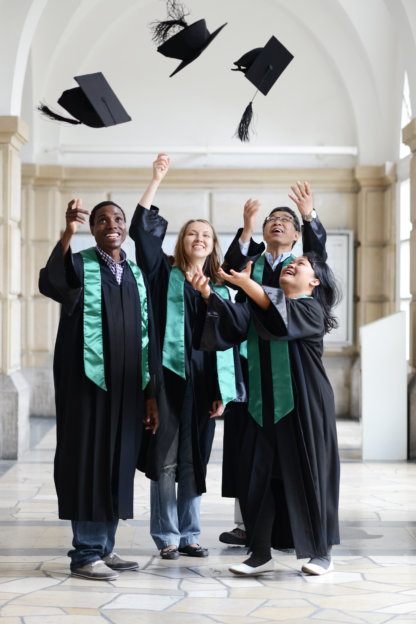 Students in a hallway throwing their academic caps into the air.