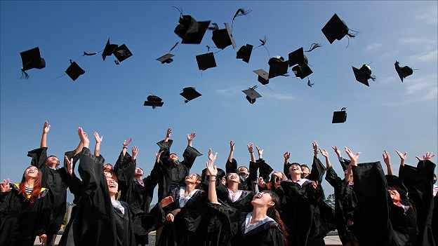 A group of graduating students in academic dress, throwing their graduation caps into the air.
