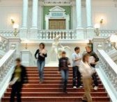 Students walking down a broad marble staircase in an elegant hall.
