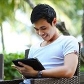 Young man smiling and looking at a tablet.