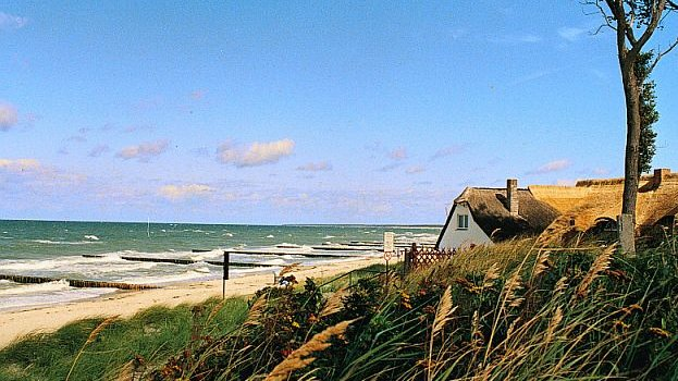 Sand dune and house at the Baltic Sea coastline in Germany.