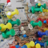 Map of Northern Europe with colorful pins tacked into different towns.