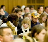 People in a lecture hall, two students talking in focus.