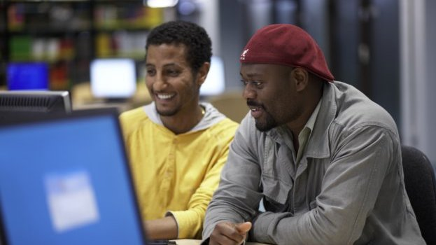 Two students looking at a computer screen smiling.